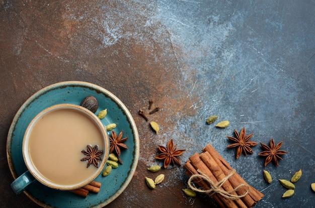 Thé indien masala chai. thé épicé au lait sur fond rouillé foncé