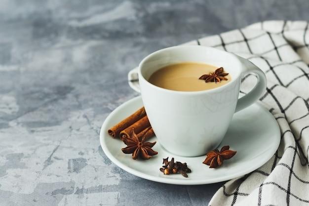 Thé indien masala chai thé épicé avec du lait sur fond de béton gris
