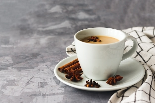 Thé indien masala chai thé épicé avec du lait sur une surface en béton gris