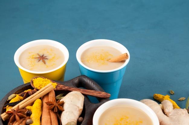 Thé indien masala (masala chai) ou lait doré dans des verres en céramique multicolores à côté des ingrédients.