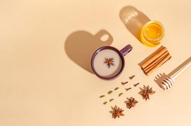Thé indien traditionnel. thé masala dans une tasse d'argile sombre avec des ingrédients, des ombres dures