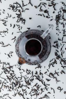 Thé infusé avec du thé noir sec dans une théière en verre sur une surface blanche, vue du dessus