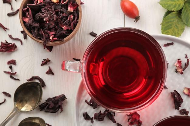 Thé karkade rouge chaud dans des tasses en verre avec du thé sur une table en bois blanc.