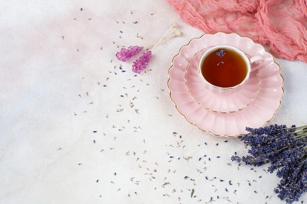 Thé à la lavande dans une tasse rose, un bouquet de lavande et de sucre violet