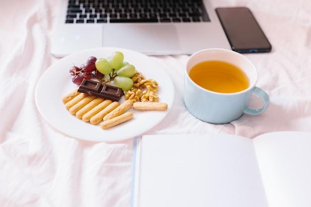 Thé à la maison dans son lit, vérification de son ordinateur portable, lecture d'un livre et petit déjeuner.