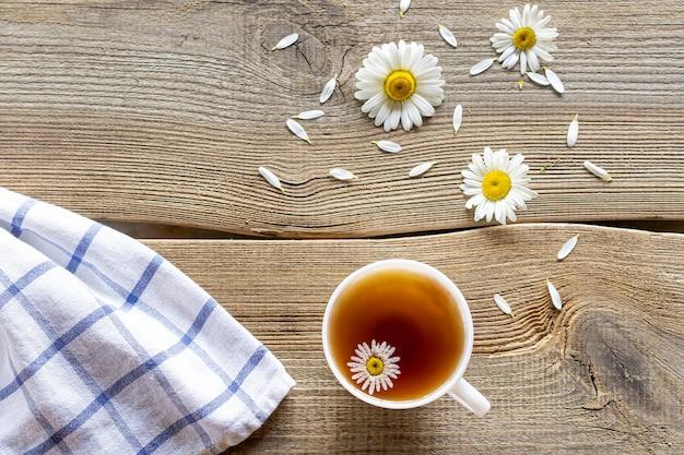 Thé de marguerite sur une table en bois avec des fleurs de marguerites à côté.
