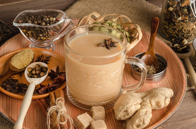 Thé masala aux épices sur une surface en bois, une boisson chaude de l'inde