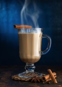 Thé masala à la cannelle et au badian sur une table en argile. un verre de thé masala sur fond bleu.