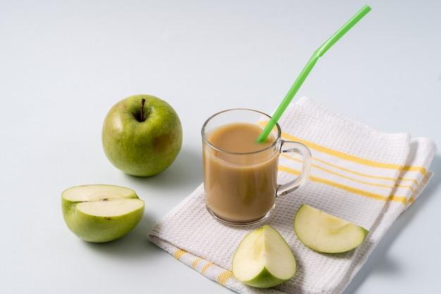 Thé masala chai dans une tasse en verre et pommes fraîches sur une table blanche.