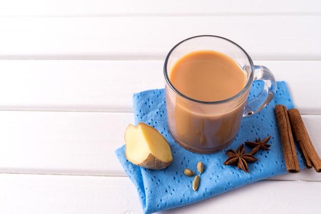 Thé masala chai dans un verre et des herbes de la cuisine sur une table blanche
