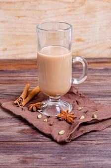 Thé masala chai indien traditionnel dans une grande tasse en verre sur une serviette sombre aux épices