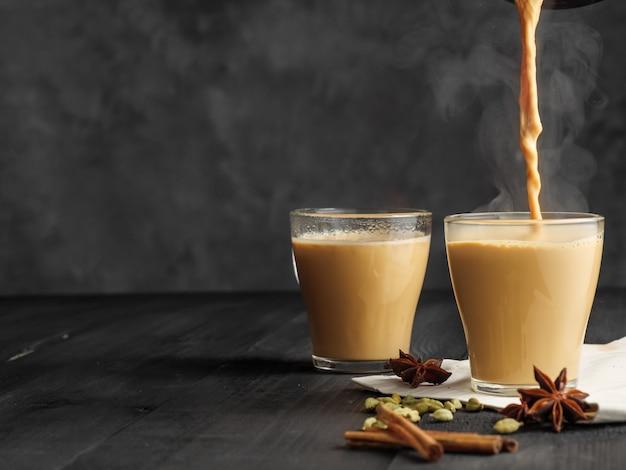 Le thé masala chaud est versé dans un verre en verre. de la vapeur sort de la tasse. fond gris.