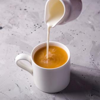 Thé masala dans des tasses minimalistes blanches sur une table grise