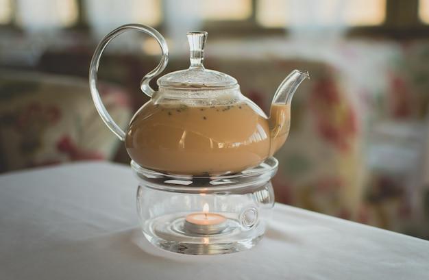 Thé masala dans une théière transparente sur une surface de café colorée.