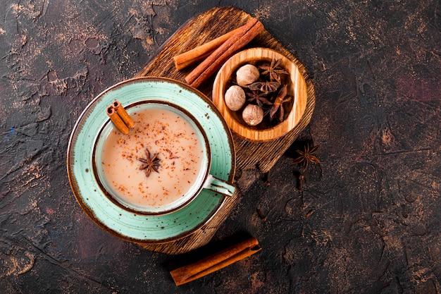 Thé masala thé traditionnel indien avec du lait et des épices dans une tasse sur la copie de vue de dessus de fond sombre