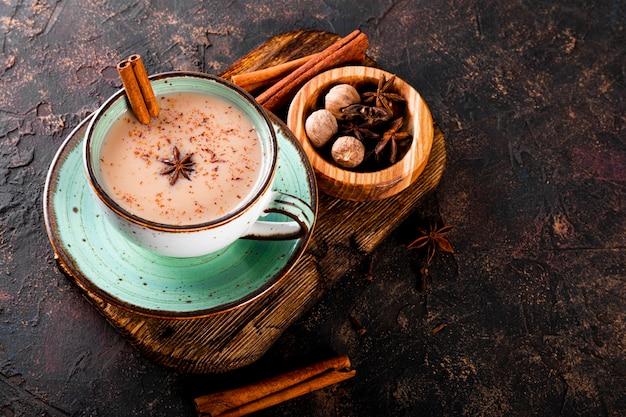 Thé masala thé traditionnel indien avec du lait et des épices dans une tasse sur l'espace de copie de fond sombre