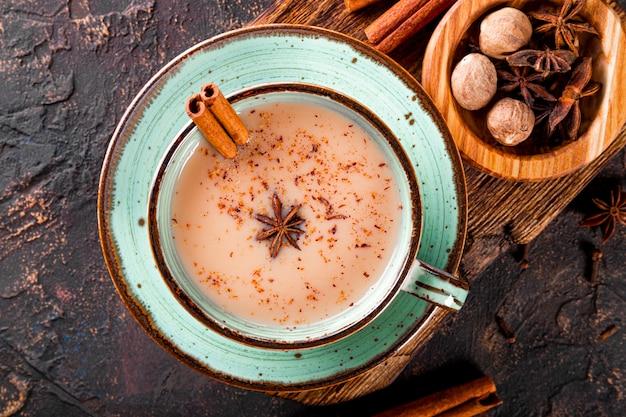 Thé masala thé traditionnel indien avec du lait et des épices dans une tasse vue de dessus en gros plan