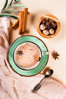 Thé masala thé traditionnel indien avec du lait et des épices dans une tasse vue de dessus photo verticale