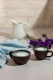 Thé matcha bleu dans un verre de latte sur la table.