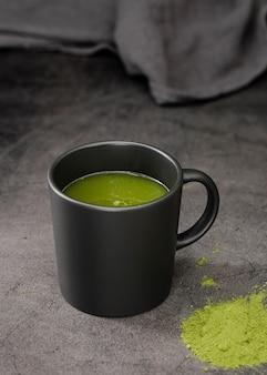 Thé matcha dans une tasse avec de la poudre