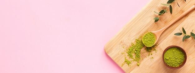 Thé matcha sur planche de bois sur fond rose