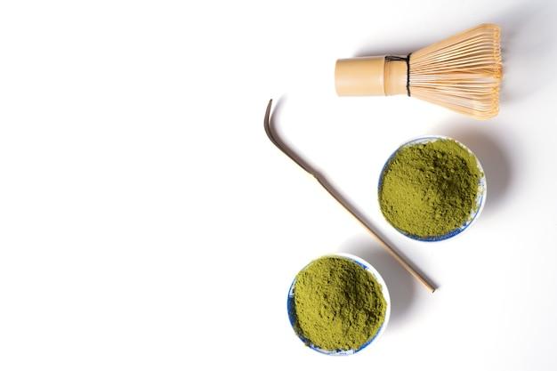 Thé matcha en poudre verte et fouet isolé sur blanc, vue de dessus, pose à plat.