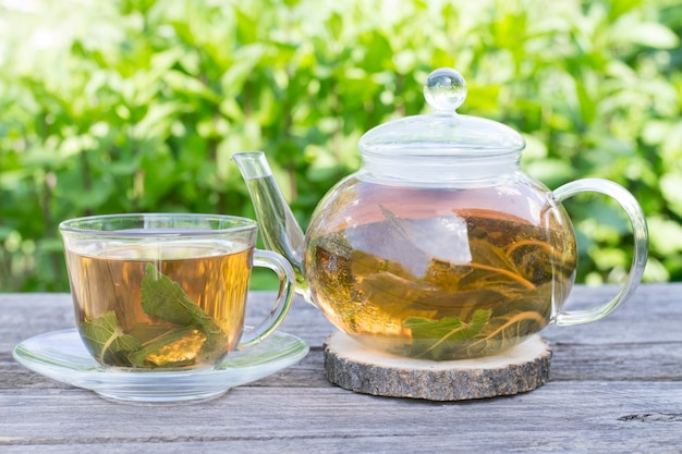 Thé à la menthe dans une théière et une tasse à l'extérieur