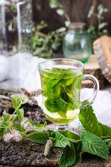 Thé à la menthe dans un verre, herbe sur une table en bois