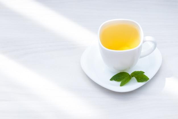 Thé à la menthe fraîche sur fond de bois blanc. mise à plat, espace copie.