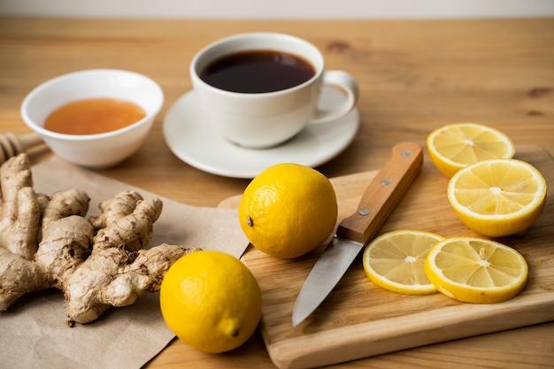 Thé, miel, citron et gingembre sur une table en bois