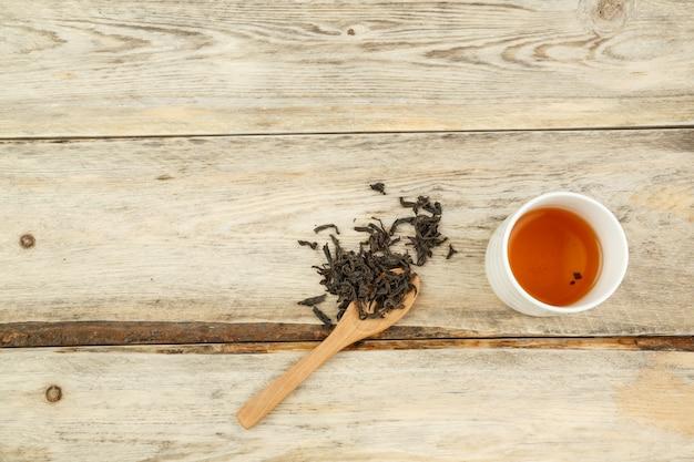 Thé naturel indien noir sur une cuillère et infusé dans un verre sur un fond en bois.