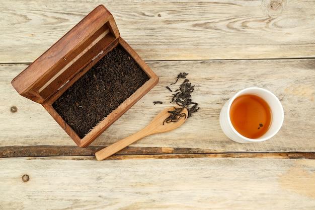 Thé naturel indien noir dans une boîte, sur une cuillère et infusé dans un verre sur un fond en bois.
