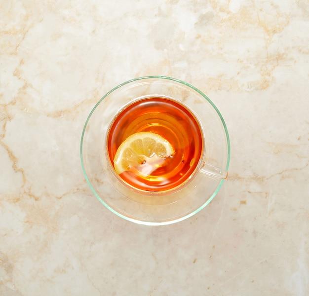 Thé noir au citron dans le mug transparent