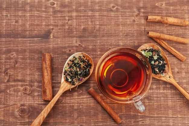 Thé noir aux herbes dans des cuillères en bois sur une planche de bois