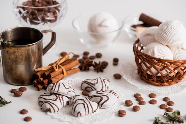 Thé noir avec des biscuits et de la cannelle sur un fond en bois blanc