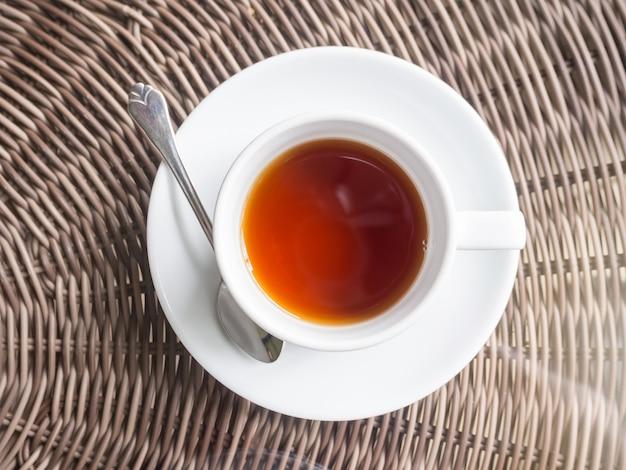 Thé noir chaud dans une tasse en céramique blanche sur une table en bois.