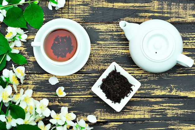 Thé noir dans une tasse blanche ronde avec une soucoupe