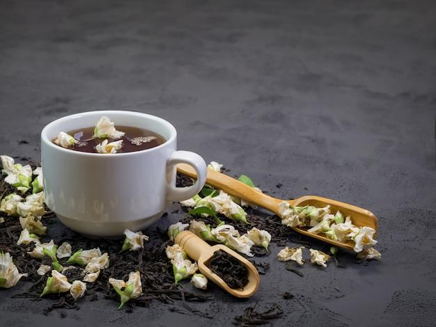 Thé noir dans une tasse blanche sur une texture noire