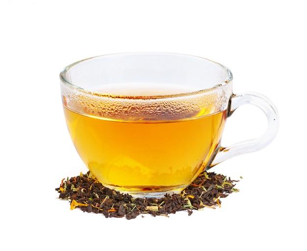 Thé noir dans une tasse de verre. feuilles de menthe et de thé. sur blanc, isolé