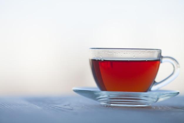Thé noir dans une tasse en verre sur fond flou.