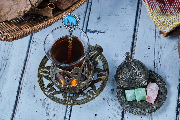 Thé noir dans une tasse en verre traditionnelle avec des bonbons sur une table en bois bleue