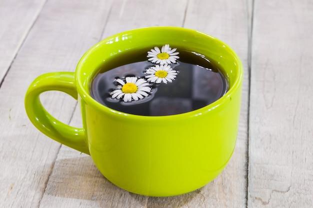 Thé noir dans une tasse verte sur fond de bois et camomille