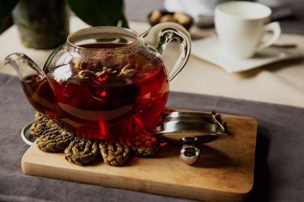 Thé noir avec des fleurs roses dans une théière en verre transparent avec une tasse, beau petit déjeuner