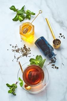 Thé noir en mug transparent en verre avec feuilles de menthe et miel thé apaisant et revitalisant antistress et détente