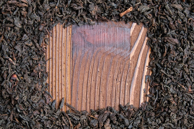 Thé noir sec sur une planche de bois brûlé.
