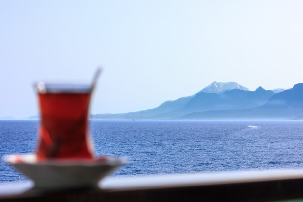 Thé noir turc en verre traditionnel sur fond de mer bleue de la méditerranée