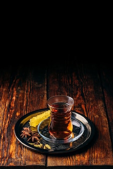 Thé noir en verre armudu avec anis étoilé et cardamome verte avec sucre cristal sur plateau en métal