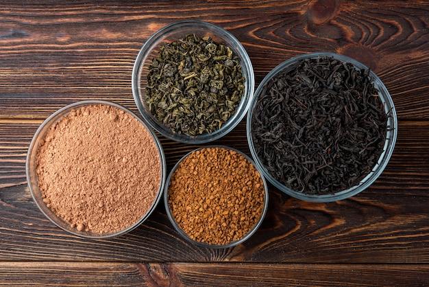 Thé noir et vert, cacao et café sur fond en bois foncé.
