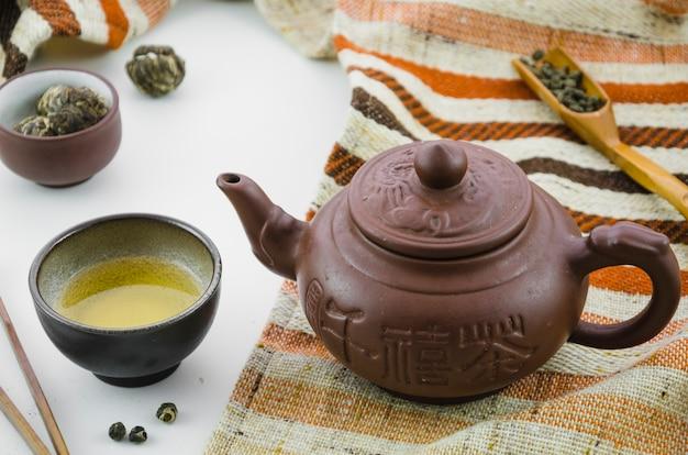 Thé oolong frais de culture asiatique et théière sur fond blanc