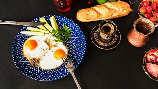 Thé, pain et omelette frite avec des tranches de concombre sur la plaque bleue